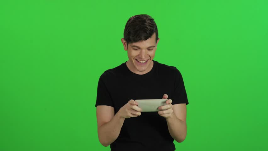 Young man in a frontal medium shot walking slowly over a green screen, texting and smiling. | Shutterstock HD Video #17589541