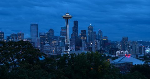 Seattle, Washington, USA - illuminated skyline of Seattle with Space needle, harbor and Elliott Bay - view from Kerry Park at sunset with clouds - Timelapse with motion and zoom out