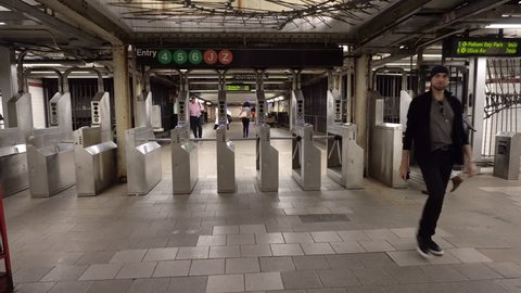 Wide Interior shot of NY subway entrance turnstiles as people swipe metrocards to pay the fare and enter the underground transit system below busy Manhattan streets (New York City - June 2016)