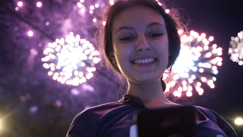 Girl use smart phone , image of firework as a background.