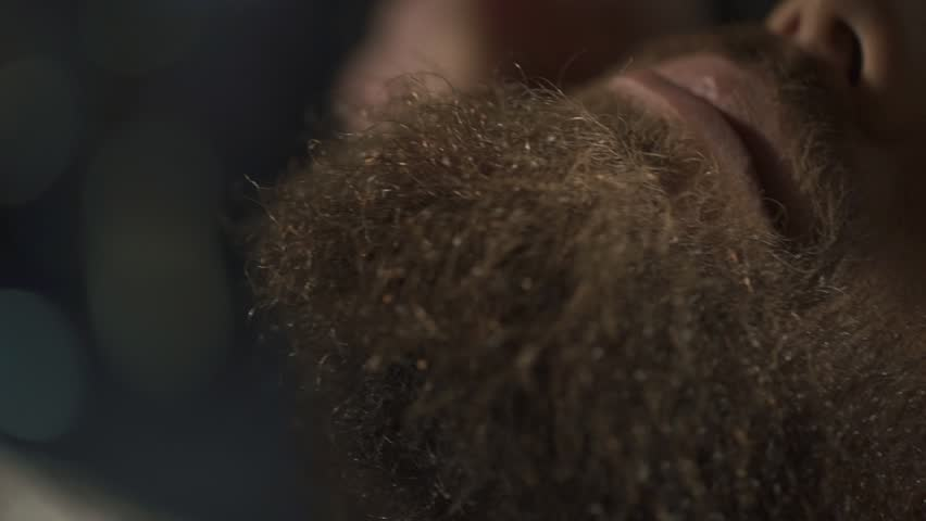 Hairstylist applying after shaving lotion in barber shop, close-up
