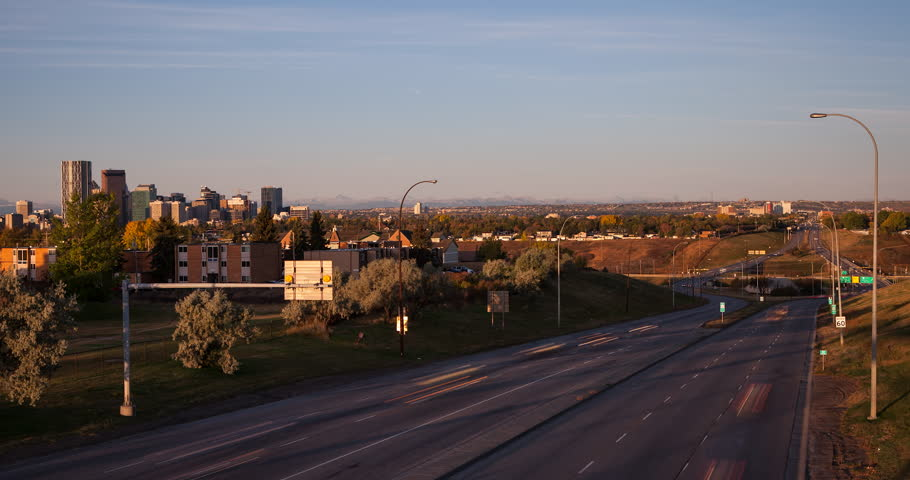 Calgary, Alberta, Canada - Crossing of Trans-Canada Highway 1 and Alberta Provincial Highway 2 with view to downtown and Canadian Rockies after sunrise - Timelapse with zoom out - October 2014