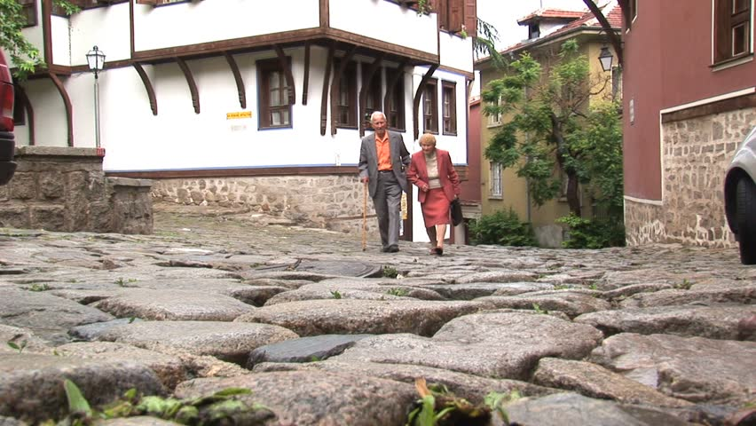 PLOVDIV, BULGARIA - CIRCA MAY 2007: An elderly couples walk across a cobblestone street circa May 2007 in Plovdiv.