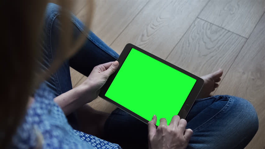 Beautiful girl using tablet pc with pre-keyed green screen sitting on the floor at home. Made from RAW source.   Shutterstock HD Video #17716096