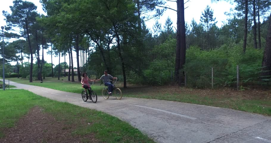 Couple cycling happily together through a sunny park  summertime  | Shutterstock HD Video #17718451