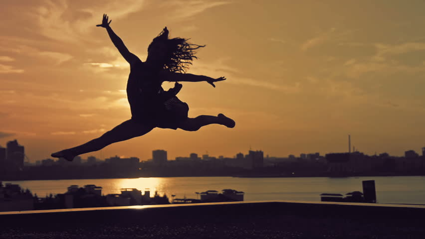 Young attractive girl with flowing hair jumping in dance at sunset silhouette