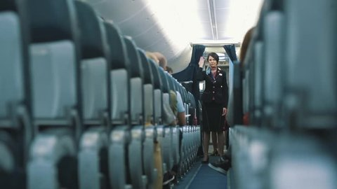 MOSCOW, RUSSIA - MARCH 17, 2016 : One unidentified female flight attendant or steward in airplane explains rules about safety with use of the belt during take off and in case of any accident or crash.