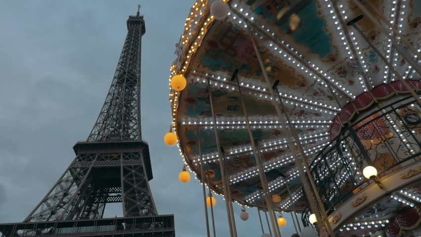 Low angle shot of spinning vintage carousel and Eiffel Tower in the evening. Visiting Paris, France