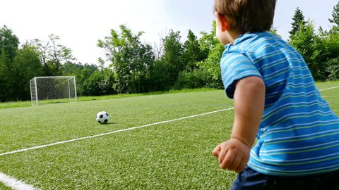 Tracking camera of a little boy scoring a goal in football field