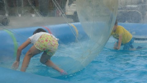 Little girl plays in a transparent bubble floating in water.