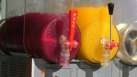 Red and yellow slushies stirring in the commercial slush machine or maker, two wasps looking for a sweet food