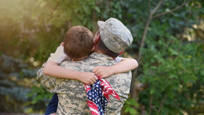 A soldier father is hugging his son holding an American flag outside for a family reunion or 4th of July concept.