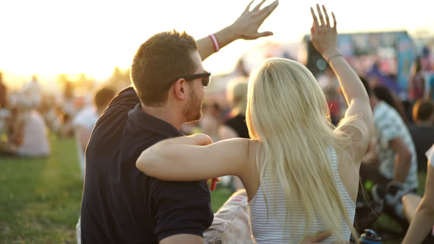 4k footage, back view young couple enjoying summer music festival at sunset, crowd and stage blurred