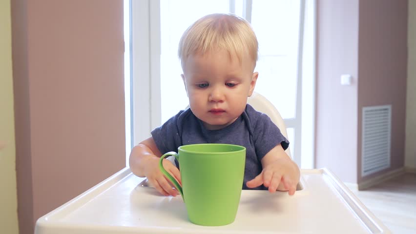 one year old Baby boy drink with pleasure water from a green cup himself. The child learns to drink from a Cup independently