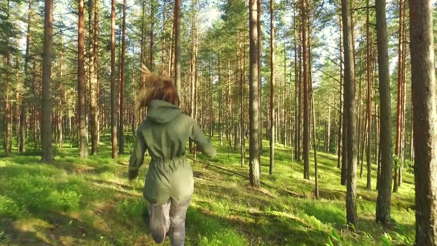 Tracking shot of young woman running through trees in forest on sunny da. Slow motion footage.