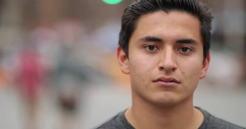 Young hispanic man in city face portrait serious