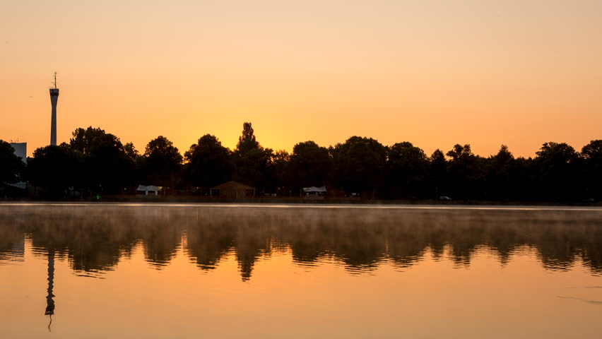 Beautiful sunrise time lapse shot with mist floating across the huge artificial lake Maschsee in Hannover, Germany.