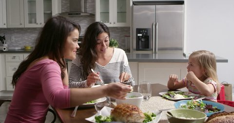 Female gay couple and daughter having dinner in their kitchen, shot on R3D