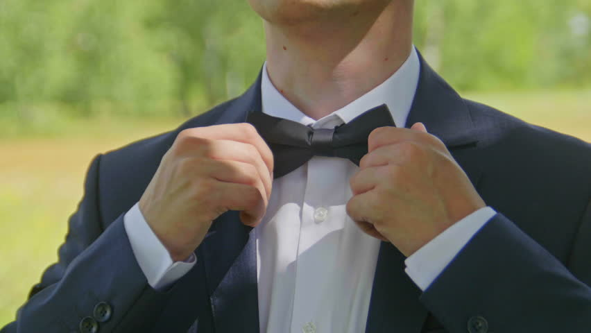 36a7f0fd2ba8 The groom in a white shirt puts on a bow tie from the front, outdoor,  closeup.