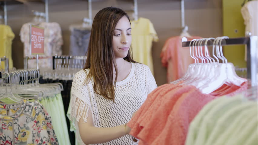 9c39f46ec07 Young woman shopping for clothes as she holds dress up to her. S. By Stock  Footage Inc