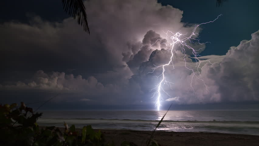 4K-UHD - Extreme lightning storm timelapse over the moonlit Florida ocean at night.