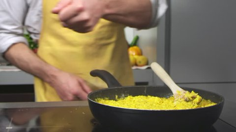 Chef cooking yellow milanese risotto and adding parmesan cheese in a modern warm kitchen