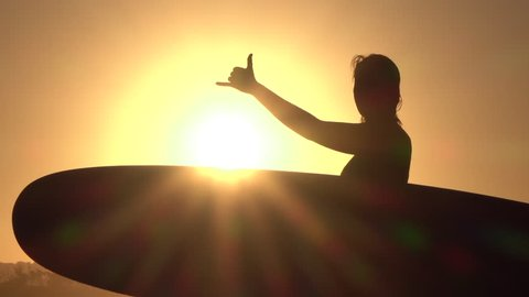 SLOW MOTION CLOSE UP SILHOUETTE: Cheerful happy young surfer girl holding longboard surfboard and doing the shaka surf culture sign gesture with fingers at golden sunset in surfing town Byron bay