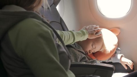 Cute little child sleeping on his seat traveling by plane. Young mother gently stroking his head.