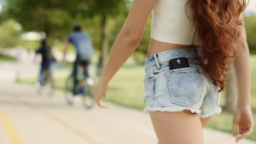 Beautiful Girl With Long Brown Curly Hair in White Top and Jean Shorts