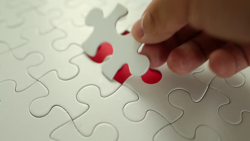 Finger put into missing pieces of puzzle