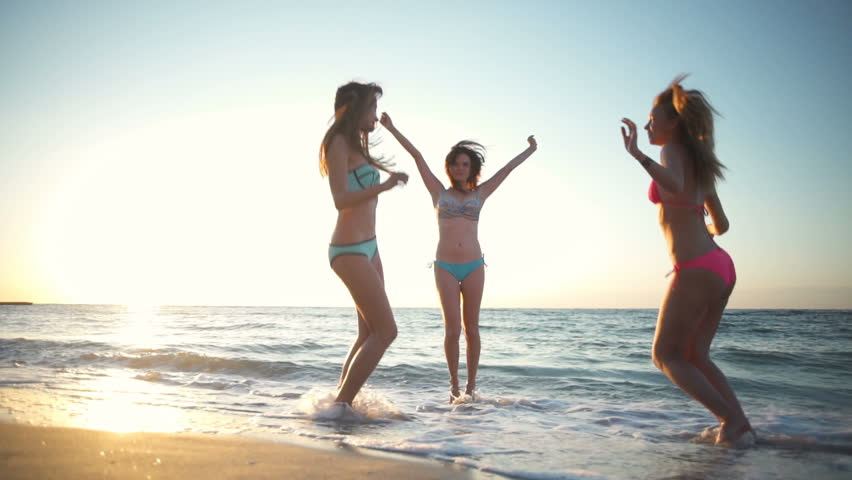 Joyful girls in swimwear having fun on the beach slow motion | Shutterstock HD Video #18101881