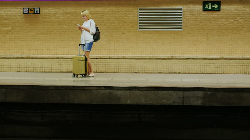Woman with travel bag waiting for a train at a subway station. use smartphones | Shutterstock HD Video #18107311