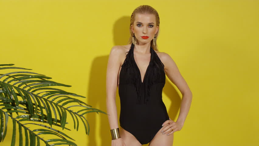 4bf9f0dde0575 Beautiful young woman posing in black swimsuit over yellow background. Sexy  blonde model in studio. Perfect slim body. Summer style - blonde beautiful  sexy ...
