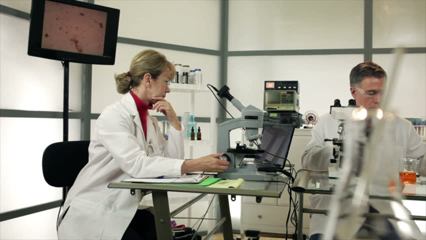 A male lab tech using a Pipette and a female researcher with a microscope camera working together in a laboratory setting. Slow dolly movement past colorful objects in the foreground.