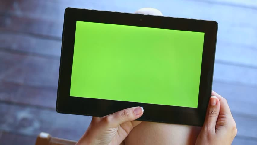 Young woman sitting over wooden background browsing internet and watching video on tablet PC with green screen. Point of view video footage of hands of anonymous woman and modern touchpad.