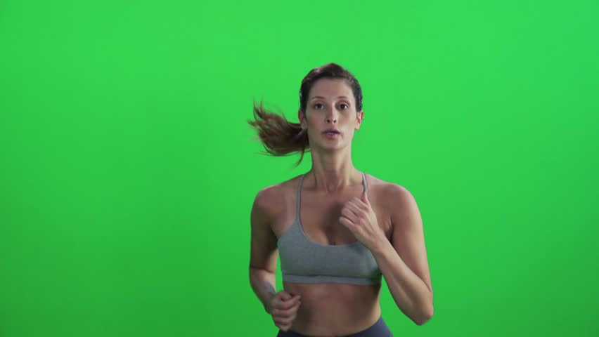 Young woman jogging in a medium frontal shot over green screen, wearing a sport bra, looking into the lens, smiles.