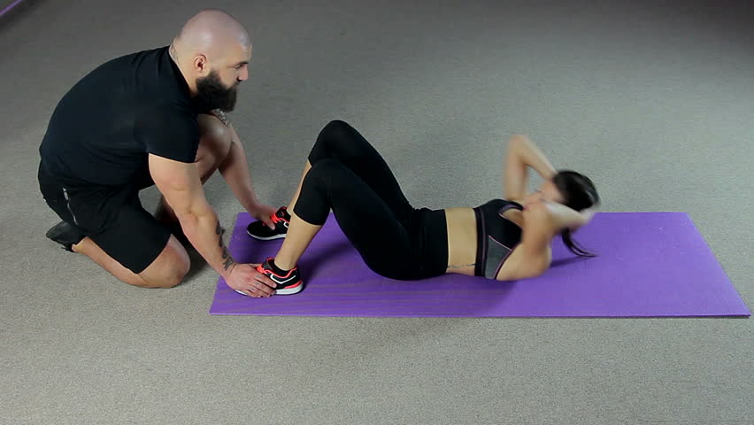 Young woman training in gym with male fitness coach, doing flat tummy exercises | Shutterstock HD Video #18142201