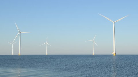 Wind turbines with rotating blades in an offshore wind park during a beautiful summer day.