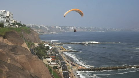 paraglider with a red canopy flies above the coast at miraflores in lima, peru