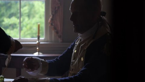 VIRGINIA - OCTOBER 2014 - Reenactment, Founding Fathers, American Revolutionary War General George Washington -- Documents, Tabletop, quill writing, dipping ink and writing by candle light & by window