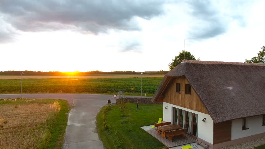 Traditional Pannonan house golden hour aerial view 4K. Flying above the old Pannonian building at sunset in background. Flat landscape panorama.