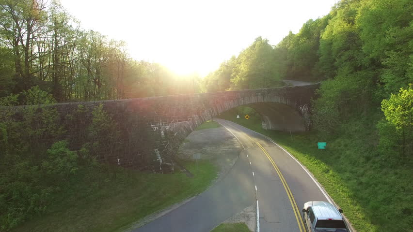 Aerial push rise flying over bridge and road of the Blue Ridge Parkway in the Pisgah National Forest in North Carolina. A truck is seen driving down the road.   Shutterstock HD Video #18240664