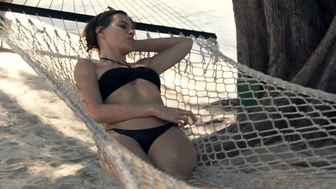 Sad, bored woman lying on hammock on beach