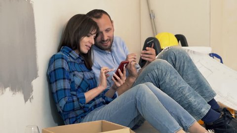 Young, happy couple talking and using smartphones on floor at their new home