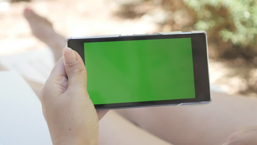Outdoor woman relaxing on deck-chair with green screen tablet 4K 2160p 30fps UHD footage - Young female holding greenscreen chroma key phone on beach 4K 3840X2160 UltraHD video