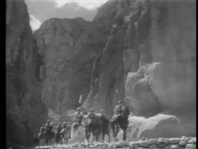 Soldiers on horseback riding through mountains