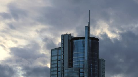 Skyscraper building / Corporate building / Clouds and Sky. Gray commercial skyscraper against dramatic sky background. Real time zoom in. (av29433c)