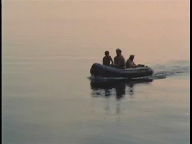 Four soldiers crossing ocean on inflatable raft