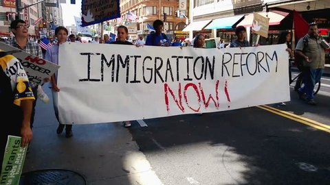 "Immigration Reform Banner. A large white picket banner that reads, ""Immigration Reform Now!"" is held up and carried by multiple people during an immigration rally in Los Angeles on September 22, 2013."