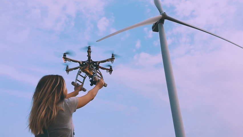 Drone takes off from the hands of a girl near a wind turbine, slow motion.